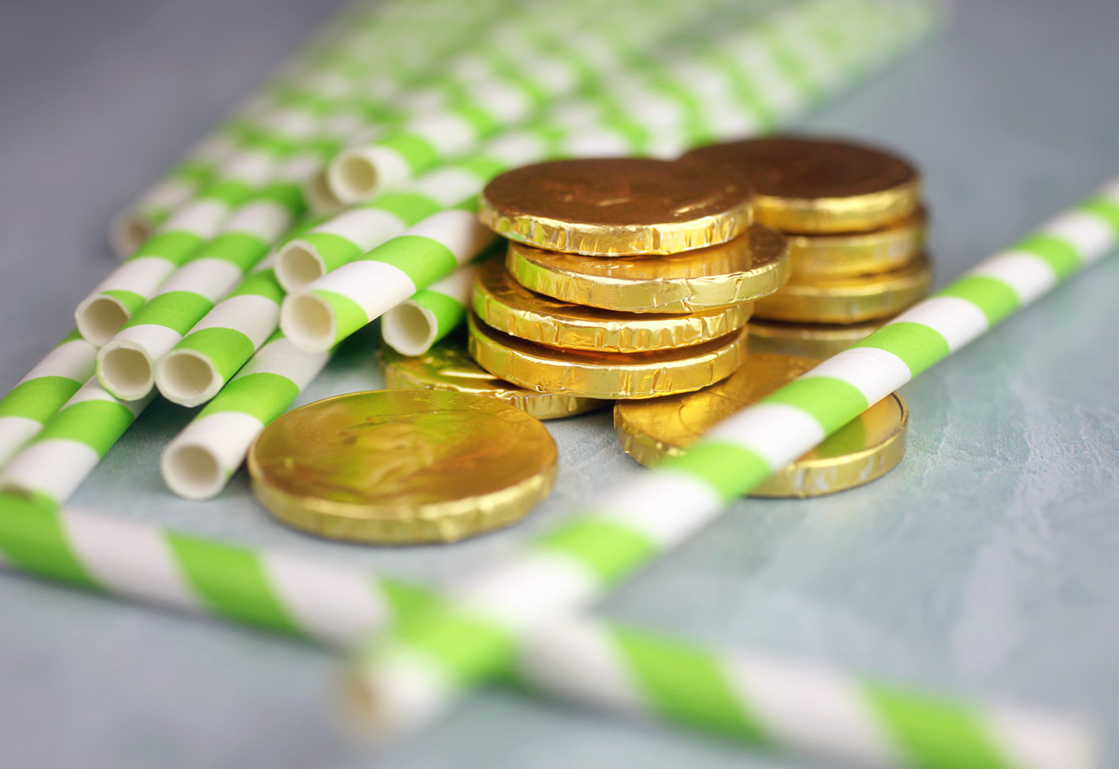 Green striped paper straws and chocolate coins
